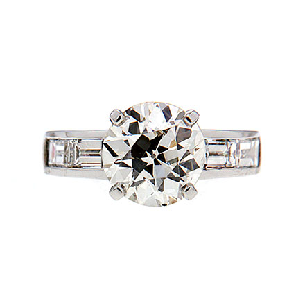Round brilliant diamond engagement ring with channel set diamond baguettes