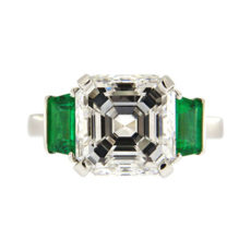 Asscher cut diamond engagement ring with emerald side stones